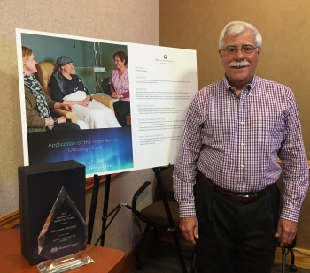 <p>MNO President Dr. Dean Gesme with the winning poster and the Innovation Partners in Excellence Award</p>